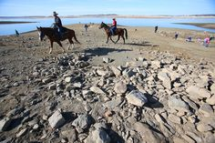 Description of . Folsom police Officers Eric Baade, left, and Daren Prociw, right, of the mounted enforcement detail  ride their horses across the exposed lake bed at Folsom Lake on Tuesday, Jan. 21, 2014 in Folsom, Calif.  (Aric Crabb/Bay Area News Group)