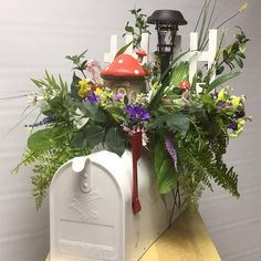 This cute mailbox topper has a mushroom house, a white picket fence and a working solar light. What a great way to distinguish your home address. The straw wreath is securely fastened to a metal topper form. Artificial flowers and moss cover this mushroom land. This will fit most