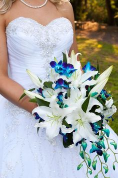 Lilies are my favorite and blue is what I've been think about for a wedding color! This is gorgeous. The dress is beautiful too #weddingflowerarrangements