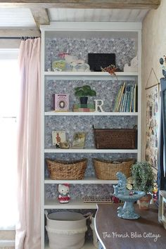 """A bookshelf with starched fabric """"wallpaper"""": a full tutorial for how to apply starched fabric to a bookcase. #starched #fabric"""