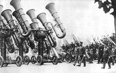 """1930s  Three Japanese acoustic locators, colloquially known as """"war tubas,"""" mounted on four-wheel carriages, being inspected by Japanese Emperor Shōwa."""