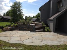 This landscape design replaced a two-story deck with an upper and lower patio separated with a curved retaining wall, a planted hillside slope, and Bluestone slab steps.