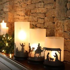 three frosted hurricane luminaries are placed on wood bases and circled with metal silhouettes of the holy family, three wisemen and shepherds.