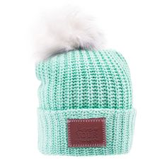 84b00434b26cb This pom beanie is knit from cotton yarn in a mint color. It features a  brown leather patch debossed with the Love Your Melon logo and a  detachable