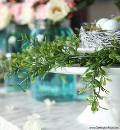 Mason jar decorating ideas. See this beautiful table set with a boxwood and bird's nest centerpiece and DIY blue tinted mason jars. Gorgeous for a wedding or dinner party!