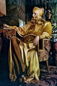 """Twiggy writing in Biba, wearing a stunning gold satin button-front ensemble, designed by Barbara Hulanick, 1973. Photo by Justin de Villeneuve. The Biba style became skinny sleeves, """"auntie colors"""" and a '20s vibe on """"fresh little foals with long legs, bright faces and round dolly eyes."""" The boutique became a staple in London. A second store opened in 1969 with an art nouveau theme. Twiggy became a big Biba patron; her big mascaraed eyes and somber look fitted the brand perfectly."""
