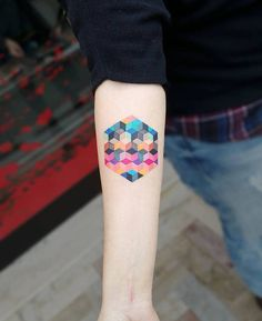 Abstract hexagon tattoo on the right inner forearm.