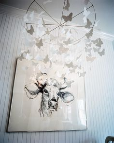 Rustic Photo - A mobile of butterflies beside a portrait of a cow