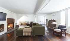 """The open-plan living room/family room/dining room has its own steel-front fireplace and original wide-plank floors. The wainscoting and ceiling coffers were built from pine trees felled and milled on the property. The living room is painted in Benjamin Moore's Decorator's White. """"My trifecta is White Dove, Decorator's White, and Super White,"""" says Givone about his favorite Benjamin Moore paints."""