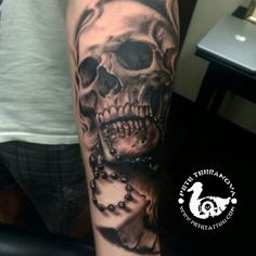 Black and gray skull and rosary tattoo