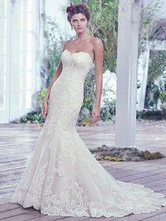Maggie Sottero - VALERIE, Lace artfully placed atop tulle adds sophistication to this feminine fit and flare wedding dress. Finished with a soft sweetheart neckline, scalloped hemline, and corset closure.