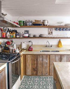 Peças de madeira de demolição (Madeireira do Vale), compradas em São João del-Rei, moldaram os armários e as prateleiras. O cimento das bancadas, executadas na obra, levou pigmento amarelo.