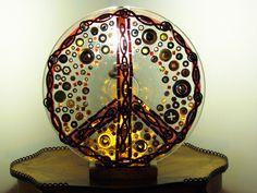 """""""PAZ"""". O símbolo da paz é apresentado numa luminária feita com correntes, arruelas, pedras e outros."""