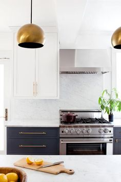 Beside white shaker upper cabinets a stainless steel hood is mounted on a honed white marble backsplash positioned over a stainless steel oven range flanked by honed white marble countertops sat atop navy blue shaker cabinets fitted with long brass pulls as a kitchen peninsula is lit by two gold pendants in this stunning white and navy blue kitchen.
