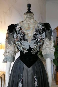 """Antique two piece reception and society dress, ca. 1906. Petersham label: """"Beer, 7 Place Vendôme, Paris * 31 Sachville Street, London W."""". Some specifications of the dress: black silk velvet and chiffon, boned bodice with bone silk lace high-neck insert and lower sleeve, decorated with"""