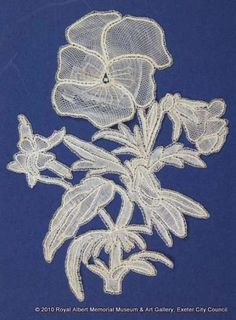 Honiton (East Devon) lace sprig - A delicate pansy or viola plant worked in East Devon bobbin lace. The open flower has been made with raised petals and veins. The petals are worked in half stitch or a combination of whole and half stitch. This is one of a series of naturalistic sprigs (lace motifs) said to have been designed and made by Louisa Tucker, a daughter of the Branscombe lace manufacturer John Tucker. Needle Lace, Bobbin Lace, John Tucker, Hm The Queen, The Royal Collection, Lacemaking, Lace Weddings, Royal Albert, Camellia