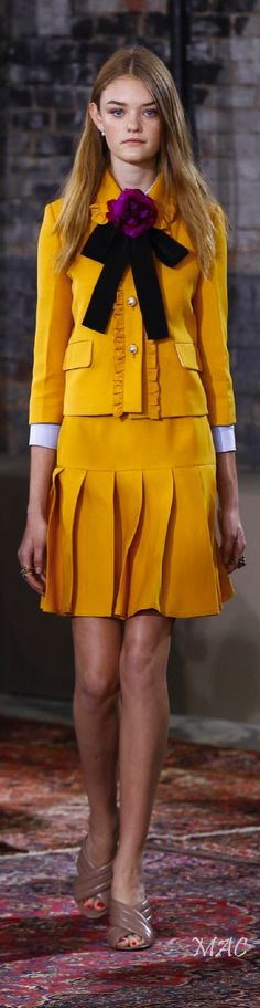 Yellow school uniform outfit with large floppy bow tie by Gucci