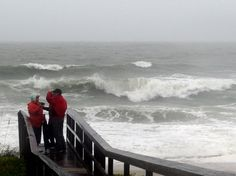 People watch the waves in a rainstorm at Atlantic Ocean at Carolina Beach, N.C., on Friday. Millions along the East Coast breathed a little easier after forecasters said Hurricane Joaquin would probably stay at sea instead of joining up with a drenching rainstorm that is bringing severe flooding to parts of the Atlantic Seaboard.