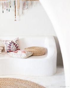San Giorgio, Mykonos, bench, throw pillows, white walls, carpet / Garance Doré