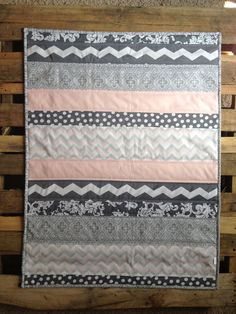 This striped baby quilt measures 30x38. Its soft colors and patterns are perfect for any nursery. It is backed with coordinating quilting fabric with a layer of natural cotton batting in between. The three layer are quilted together in a stitching pattern specific to the quilt to prevent shifting and to keep the layers secure for the long life of the quilt. Also available in baby blue. All products are made personally with love. All quilts are unique and individually patterned just for you…