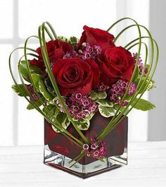 Deep red roses, artistically placed greens, square glass cube vase...beautiful