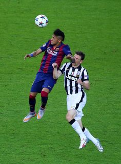 Neymar of Barcelona outjumps Stephan Lichtsteiner of Juventus during the UEFA Champions League Final between Juventus and FC Barcelona at Olympiastadion on June 6, 2015 in Berlin, Germany.