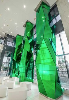 The three 10 meter high feet) structural concrete columns are each clad with 40 faceted glass panels. Mall Design, Retail Design, Store Design, Folding Architecture, Interior Architecture, Interior Design, Signage Design, Facade Design, Hospital Architecture