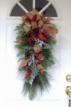 Christmas Swag-Christmas Cardinal Wreath-Christmas Wreath for Front Door-Holiday Swag for Door-Winter Wreath with Cardinal-Berry Wreath  This lovely holiday swag features a realistic red cardinal perched on a snowy branch. Loads of realistic evergreens, including long-needled white pine, hemlock, Colorado spruce, and frosty cedar make a lush and full display. Snow-tipped red berries, pine cones, rusted bell and pine cone sprays add to the festive look. The design is finished with a double…