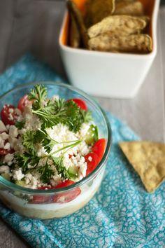 This dip is FULL of layered flavors (hummus, creamy greek yogurt, fresh veggies and herbs and a sprinkle of feta).