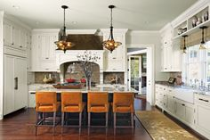 White cabinets and orange counter stools in kitchen designed by Murphy & Co. Design. Photo by Susan Gilmore.