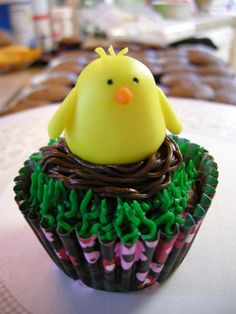 Springtime fondant chick in a nest of chocolate buttercream on top of a grassy cupcake.