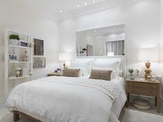 Branco total no quarto de casal, com elementos tom cru e móveis em madeira fazendo o contraponto.