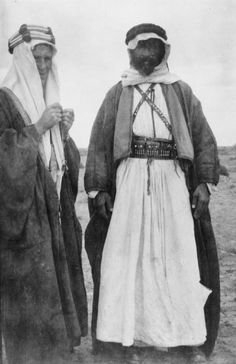 Lawrence, wearing Arab dress, in conversation with Auda abu Tayi, leader of the Howeitat tribe, in the desert. 1917
