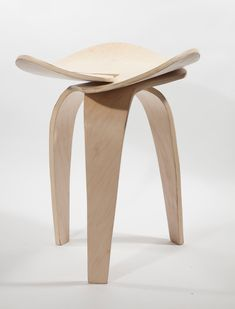 A sculptural stool made of three symmetrical pieces of bent plywood that connect together into a jointless minimal form creating a support system.