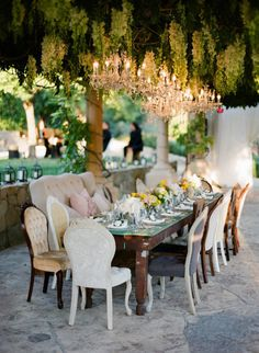 Outdoor Dining.  Couch & mixed chairs.  Chandeliers.  Additional ambient lighting surrounding.  Draping around patio to create intimacy.