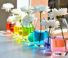 23 arranjos de flores para deixar qualquer ambiente mais especial: 18- Arranjo com água colorida. Colorir a água é uma sugestão prática para quem não tem tempo de pintar os vasos. Para evitar que as flores absorvam a cor, coloque-as no recipiente poucos minutos antes do evento em que serão empregadas na decoração.