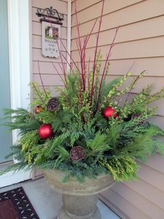 Christmas outdoor container full of evergreens, red twigs and ornaments - uploaded to Pinterest.
