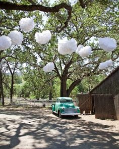 Paper pom-poms strung from tree branches add whimsical charm to this rustic barn wedding