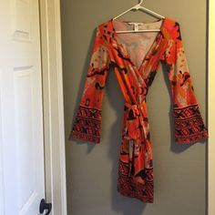 DVF wrap dress Multicoloured and coveted Diane Von Furstenberg wrap dress in orange, tan, teal and a bit of burgundy. Very striking with it's own belt of the same fabric. Worn very gently, only a few times in good condition. Diane von Furstenberg Dresses Long Sleeve