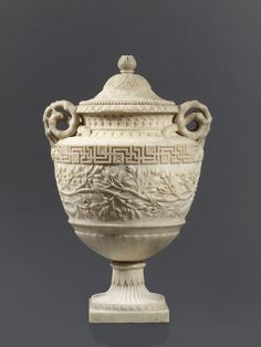 A Fine Italian Neoclassical Carrara Marble Lidded Vase after the Antique, First Quarter 19th Century. The spreading domed lid with leafy knop above a leaf-carved neck with double-scroll handles in the form of olive branches, the body decorated with a Greek-key and rosette frieze above berried laurel-leaf spraus and birds and gadrooned base raised on a leaf-carved and fluted round spreading base wih Vitruvian scroll edges on a square plinth - Dim: H: 87 cm (34 ½ in.) W: (max.): 55 cm (21 ½…