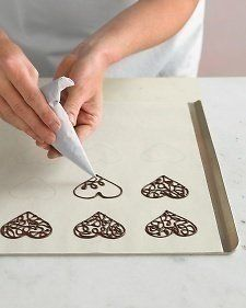 Use melted chocolate chips and a ziploc bag to pipe filigreed chocolate shapes onto parchment paper. No special tools required (other than a steady hand, of course)Freeze the chocolate designs, then peel off parchment and use to garnish cakes