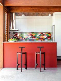 Do colorido painel de azulejos (Lurca), saíram algumas referências para definir os tons da bancada e das alvenarias de outros ambientes. No piso, cimento queimado executado na obra. Projeto do escritório AMZ.