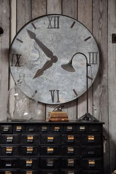 A perfectly aged vintage clock face makes a dramatic art piece hanging on the grey wood wall.