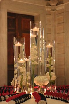 Centerpiece Arrangement: Collection of submerged gladiola stalks topped by floating candles surrounded by petite hydrangea arrangements.