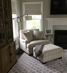 Beautiful and cozy corner of this home designed by Susan Arlio. The chair and a half with its matching ottoman is dressed in a beautiful stripe, complimenting the geometric rug and transitional floor lamp. The English arm ties it all together, keeping it classic and simple, while still being stylish and functional.