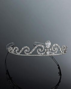 A exceptional belle époque diamond tiara,circa 1905 the old European-cut diamond scroll centering a bezel-set old pear-shaped diamond weighing 7.26 carats; remaining diamonds weighing approximately: 25.70 carats; mounted in platinum.