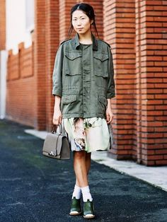 An army jacket is worn with a floral knee-length skirt, top handle bag, peep-toe heels and socks