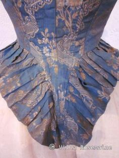 """Detail back view, """"Pierrot à la hussarde"""" jacket, France, 1780-1790. Nattier blue silk taffeta with a woven pattern of bouquets, trimmed with ivory silk ribbon on the pass, steel buttons on each wrist, linen lining."""