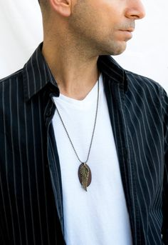This pendant necklace is made of Oxidate silver ball chain and oval brown leather with brass angel wing pendant. The necklace is 38 cm (14.96)