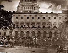 A city in mourning---the Capitol in Washington befitted with mourning crepe in honor of A. Lincoln. Photo attributed to Matthew Brady, 1865.